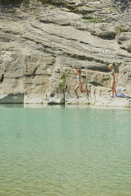 Girls jumping onto beautiful blue freshwater