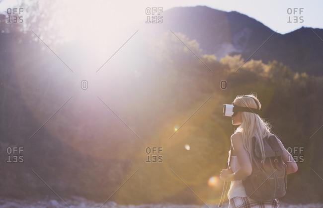 Woman wearing VR headset in outdoor landscape