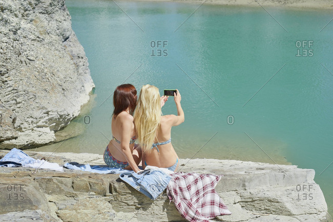 Beautiful friends taking smart phone selfies