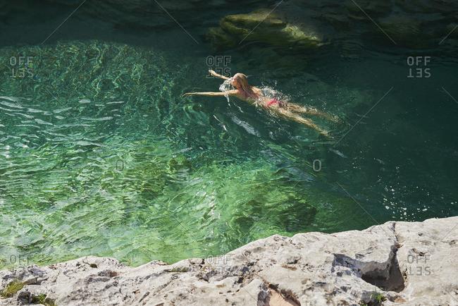 Woman swims through blue river