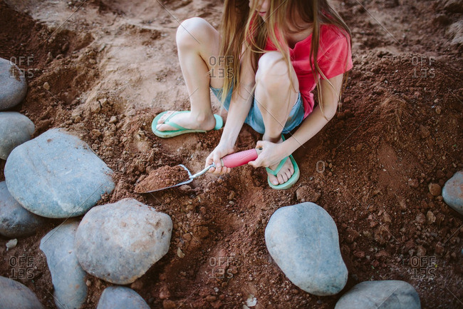 Young girl playing in the dirt