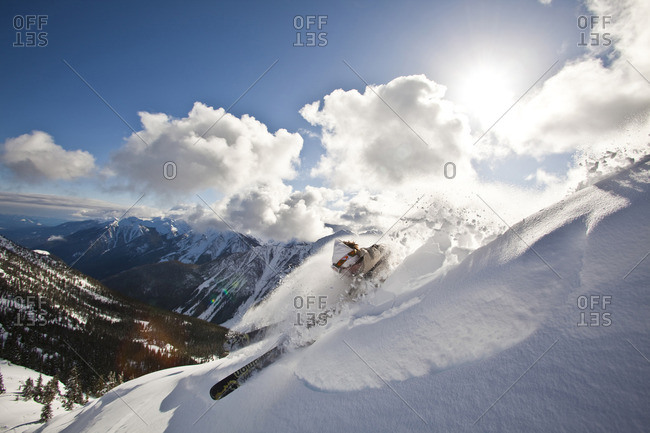 British Columbia, Canada - February 17, 2010: A young male skier slashes a powder turn, Kicking Horse Resort