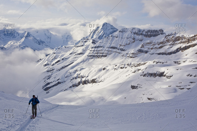 A man follows a skin tack up into the alpine for a day of ski mountaineering. Icefall Lodge, Golden, British Columbia, Canada