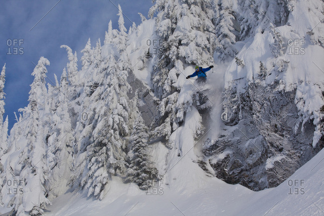 A male skier catches some air off a cliff in the Revelstoke Mountain Resort Backcountry, Revelstoke, BC