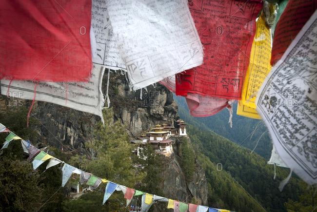 Taktsang (Tigers Nest) Monastery peeks out behind some prayer flags above Paro, Bhutan
