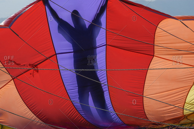 A parasailing crew member is silhouetted holding a parachute preparing to lift a client skyward off the Vietnamese coast of Nha Trang