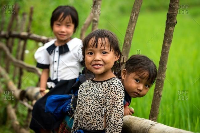 Mu Cang Chai, Vietnam - January 13, 2017: Happy Vietnamese kids standing at wooden fence