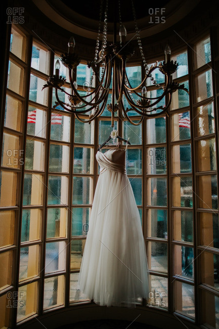Bridal gown hanging from chandelier