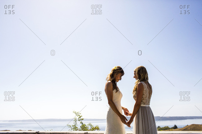 Caucasian brides holding hands at waterfront