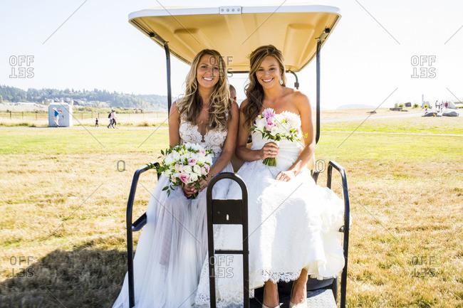 Caucasian brides sitting in golf cart