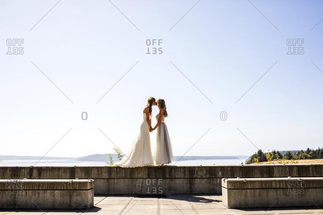 Caucasian brides kissing at waterfront