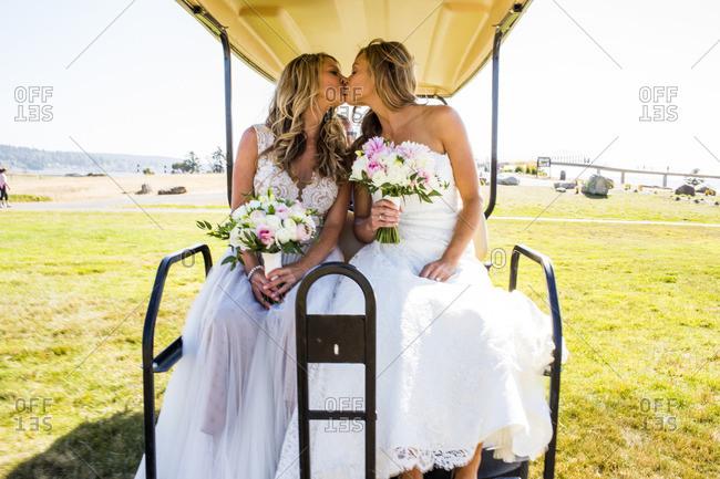 Caucasian brides kissing in golf cart