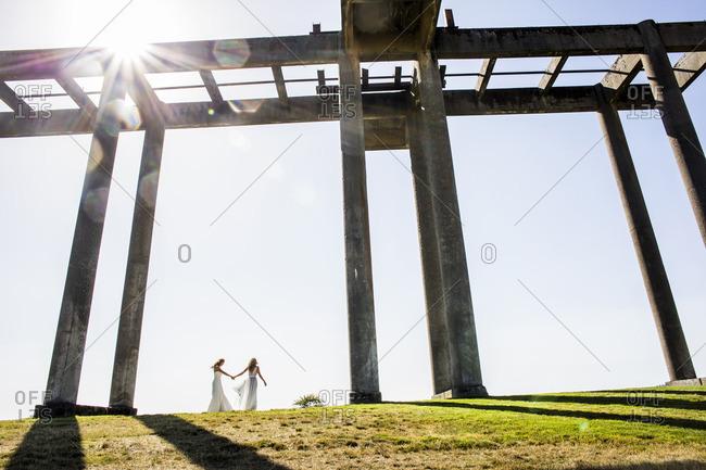 Caucasian brides holding hands walking under concrete structure
