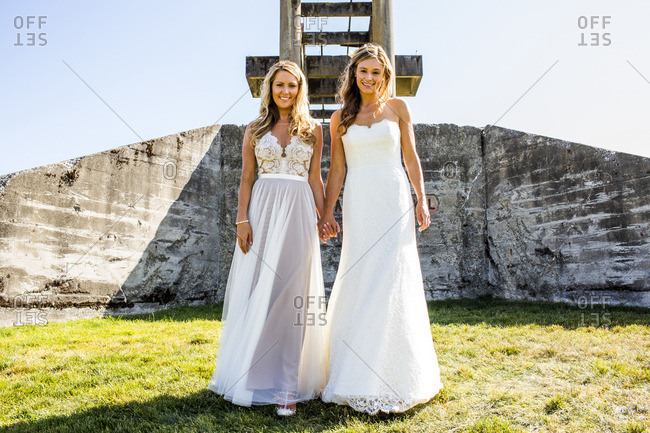 Caucasian brides holding hands in grass near concrete structure