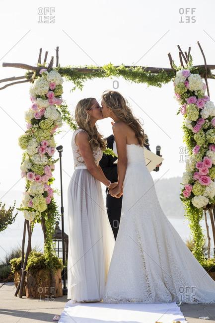 Caucasian brides kissing at wedding ceremony