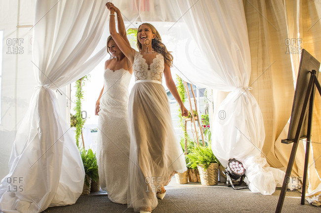 Caucasian brides walking through curtain
