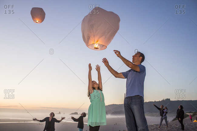 Caucasian father and daughter flying lantern balloon at beach