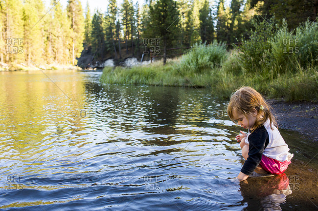 Caucasian girl crouching in river