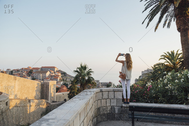 Caucasian woman standing on park wall photographing cityscape