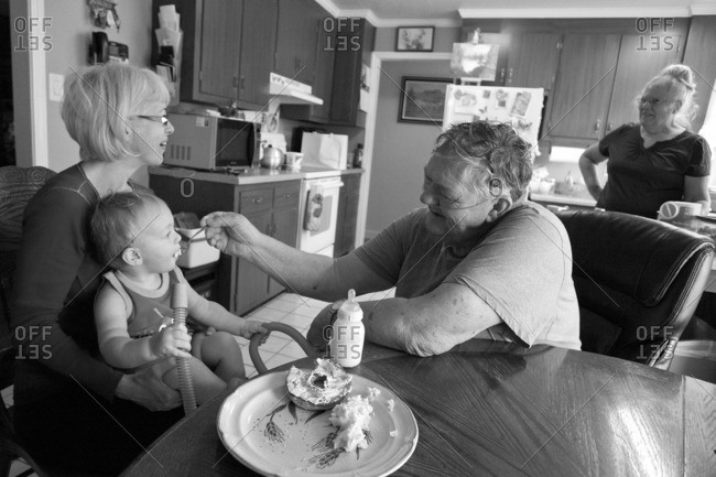 Caucasian grandfather feeding grandson in kitchen