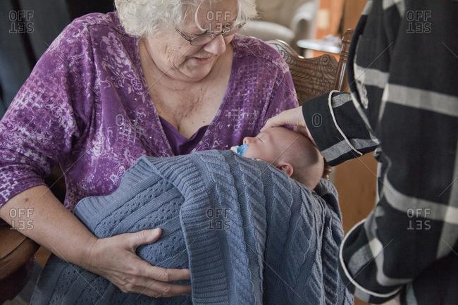 Caucasian grandmother holding baby grandson