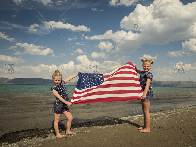Caucasian girls holding American flag at beach