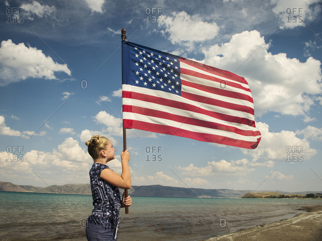 Caucasian girl holding American flag at beach