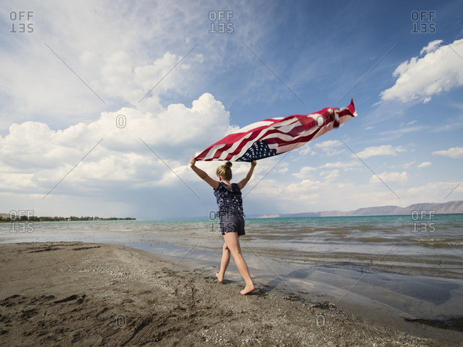 Caucasian girl walking with American flag at beach