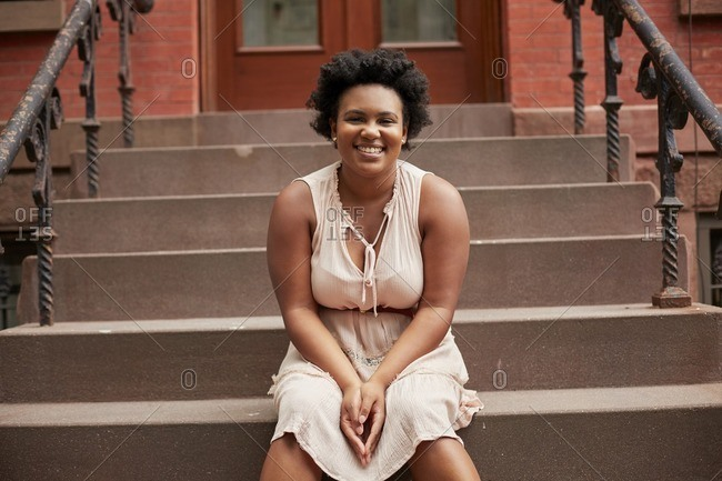 Portrait of smiling Black woman sitting on urban front stoop