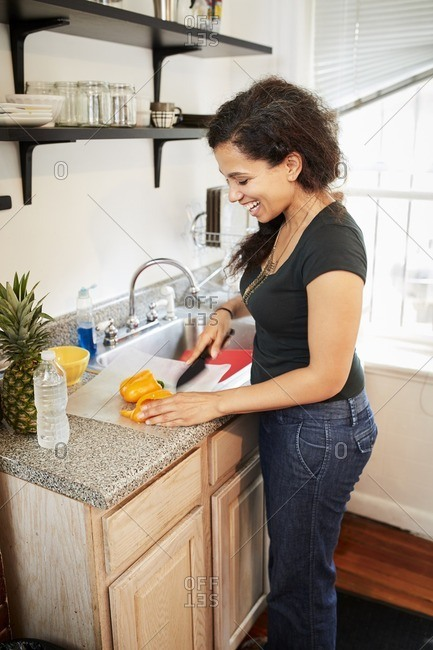 Smiling Mixed Race woman chopping pepper on cutting board