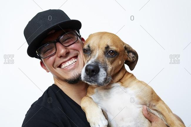 Smiling Hispanic man hugging dog
