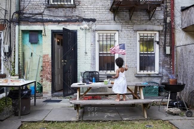 Mixed Race girl standing on backyard bench waving American flag