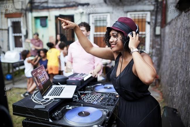Mixed Race young woman djing music at backyard party