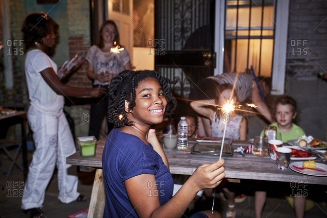 Smiling girl holding burning sparkler at backyard party