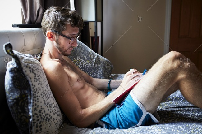 Caucasian man sitting on bed writing in journal