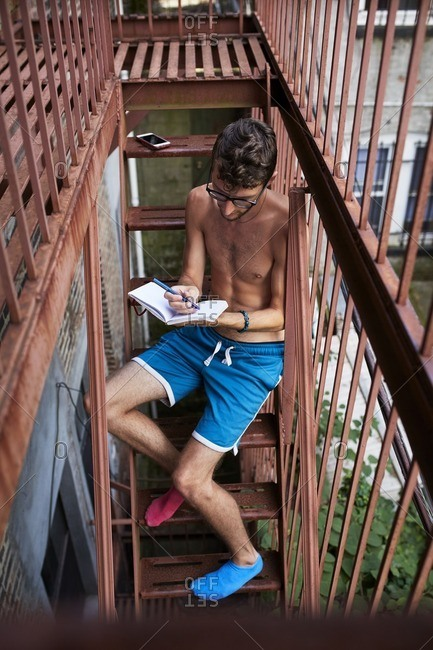 Caucasian man sitting on urban fire escape writing in journal