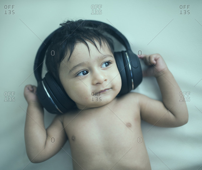 Indian baby boy listening to headphones