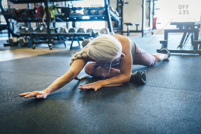 Caucasian woman stretching on gymnasium floor