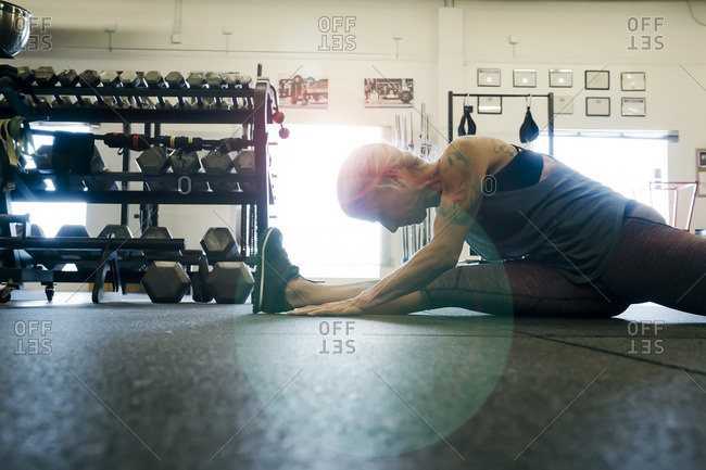 Caucasian woman stretching leg on gymnasium floor