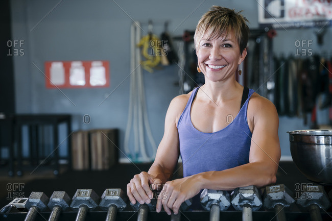 Smiling Caucasian woman leaning on rack in gymnasium