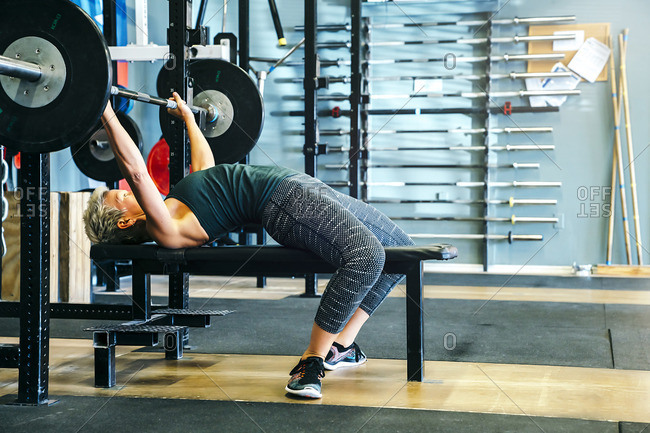 Caucasian woman lifting barbell on bench in gymnasium
