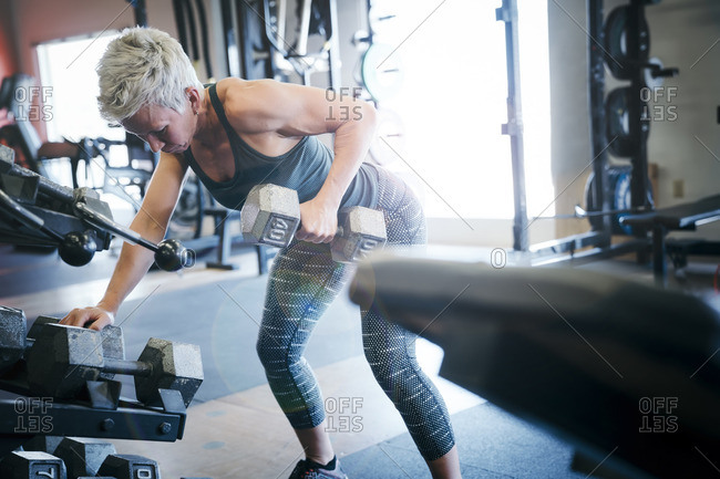 Caucasian woman lifting barbell in gymnasium