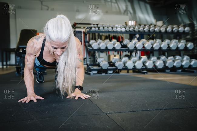 Caucasian woman doing push-up in gymnasium