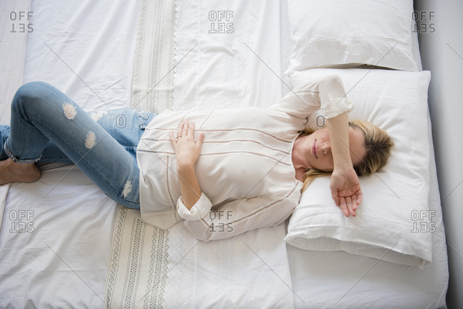 Caucasian woman laying on bed covering eyes