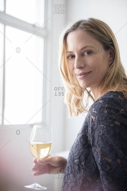 Caucasian woman drinking white wine