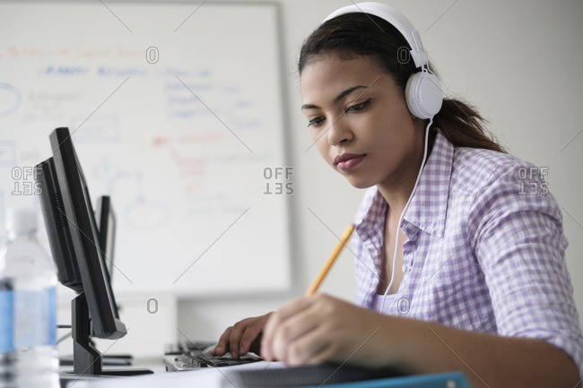 Hispanic woman in computer lab writing in notebook