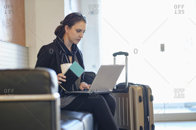 Hispanic woman holding passport using laptop in airport
