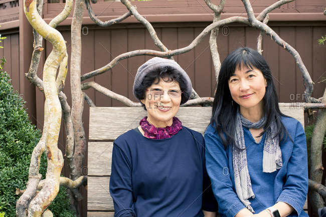 Older Japanese mother and daughter sitting on wooden bench