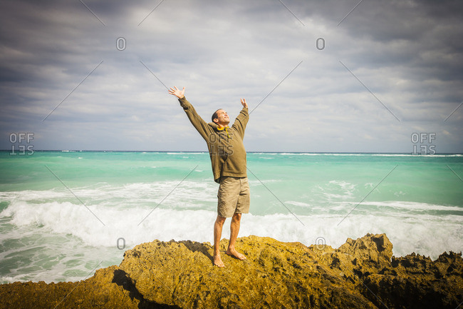 Caucasian man standing on rocks at ocean with arms raised