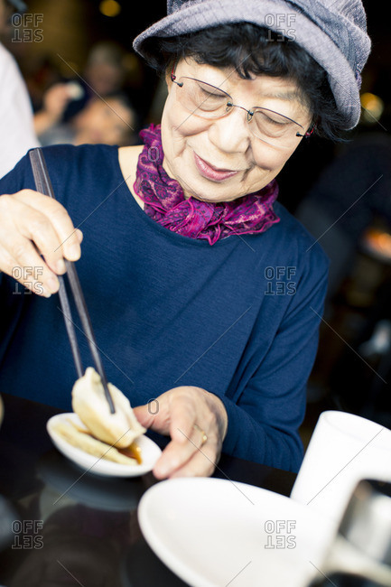 Older Japanese woman eating food with chopsticks
